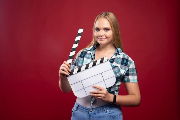 Blonde vrouw met een filmproductie klepel bord en ziet er positief en leuk uit.