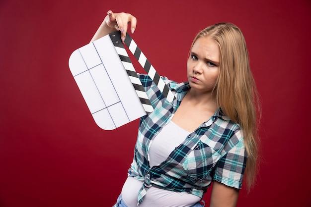Blonde vrouw met een filmproductie klepel bord en ziet er verward en moe uit.