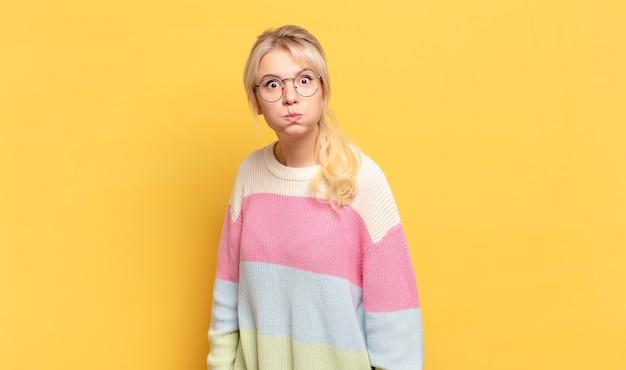 Blonde vrouw met een gekke, gekke, verbaasde uitdrukking, puffende wangen, zich gevuld, dik en vol eten