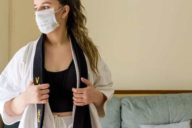 Blonde vrouw met een masker thuis karate beoefenen