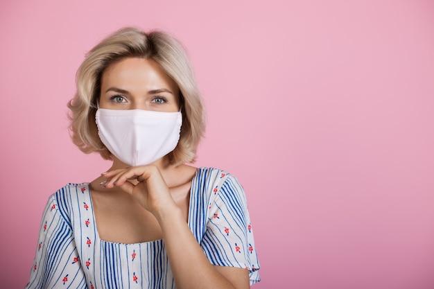 Blonde vrouw met een medisch masker op gezicht camera kijken terwijl ze een jurk draagt en haar kin aanraken op een roze studiomuur met vrije ruimte