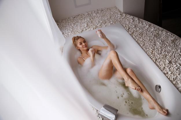 Blonde vrouw met een mooi figuur ligt in de badkamer met schuim en glimlacht