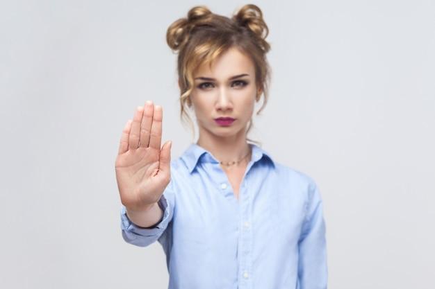 Blonde vrouw met een slechte houding die een stopgebaar maakt met haar handpalm naar buiten, nee zegt, ontkenning of beperking uitdrukt. studio opname