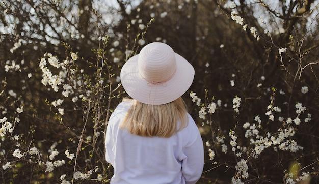 Blonde vrouw met een witte hoed met bomen op de achtergrond