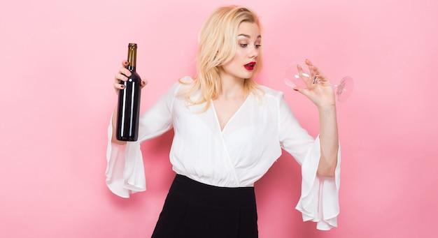 Blonde vrouw met fles wijn en glas