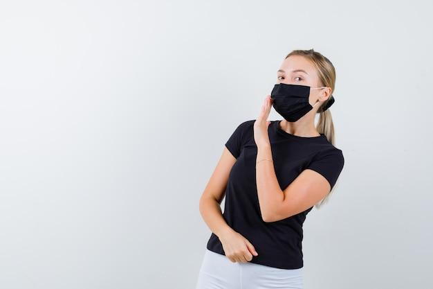 Blonde vrouw met hand in de buurt van mond om geheim te vertellen in zwart t-shirt