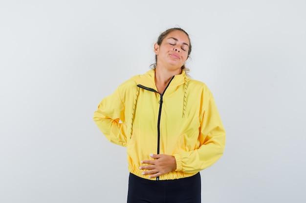 Blonde vrouw met hand op buik en buikpijn in geel bomberjack en zwarte broek en uitgeput op zoek