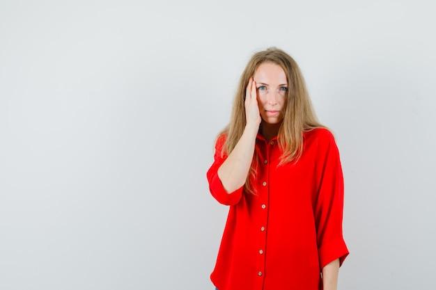Blonde vrouw met hand op wang in rood shirt en op zoek kalm,