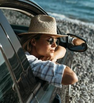 Blonde vrouw met hoed en zonnebril kijkt uit autoraam