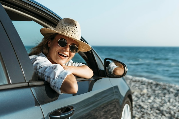 Blonde vrouw met hoed kijkt uit autoraam