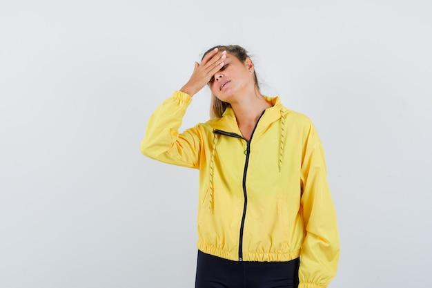 Blonde vrouw met hoofdpijn in geel bomberjack en zwarte broek en ziet er moe uit