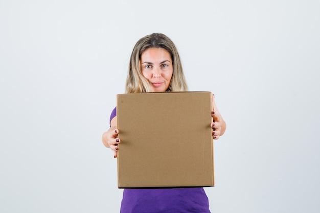 Blonde vrouw met kartonnen doos in violet t-shirt vooraanzicht.