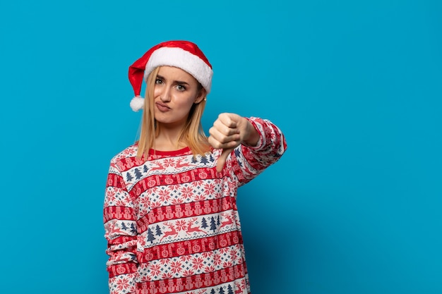 Blonde vrouw met kerstmuts die zich boos, boos, geïrriteerd, teleurgesteld of ontevreden voelt, duimen naar beneden met een serieuze blik