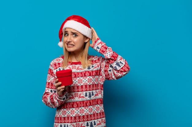 Blonde vrouw met kerstmuts die zich gestrest, bezorgd, angstig of bang voelt, met de handen op het hoofd, in paniek raakt bij een fout