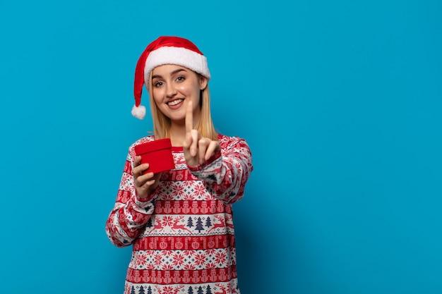 Blonde vrouw met kerstmuts glimlachend trots en zelfverzekerd nummer één pose triomfantelijk, gevoel als een leider