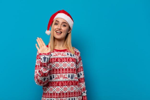 Blonde vrouw met kerstmuts lacht vrolijk en vrolijk, zwaait met de hand, verwelkomt en begroet je, of neemt afscheid