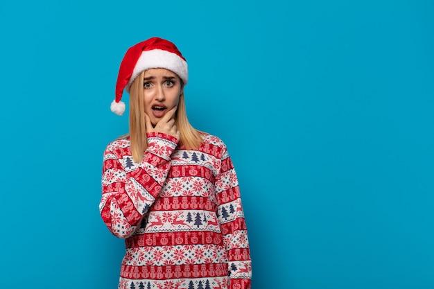 Blonde vrouw met kerstmuts met mond en ogen wijd open en hand op kin, onaangenaam geschokt