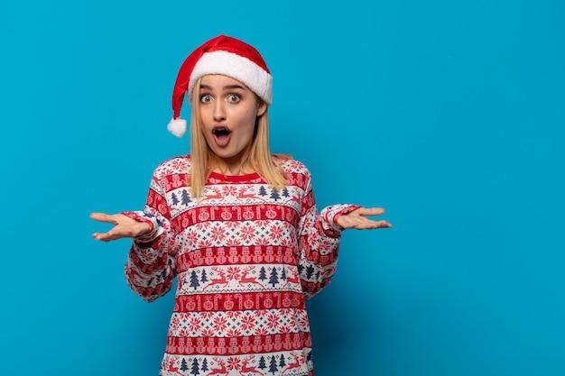 Blonde vrouw met kerstmuts met open mond en verbaasd, geschokt en verbaasd over een ongelooflijke verrassing