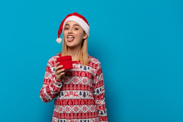 Blonde vrouw met kerstmuts met vrolijke, zorgeloze, rebelse houding, grapje en tong uitsteekt, plezier maken