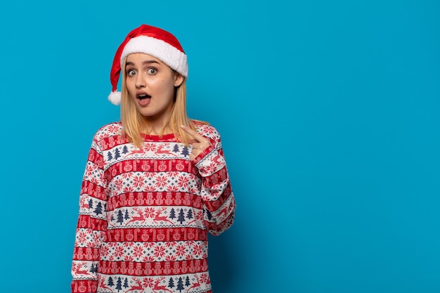 Blonde vrouw met kerstmuts op zoek geschokt en verrast met wijd open mond, wijzend naar zichzelf