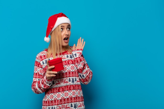Blonde vrouw met kerstmuts voelt zich blij, opgewonden en verrast, naar de zijkant kijkend met beide handen op het gezicht