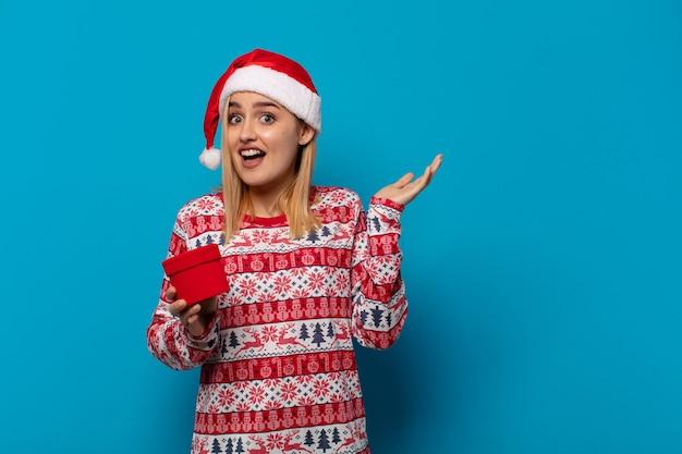 Blonde vrouw met kerstmuts voelt zich blij, opgewonden, verrast of geschokt, glimlachend en verbaasd over iets ongelooflijks