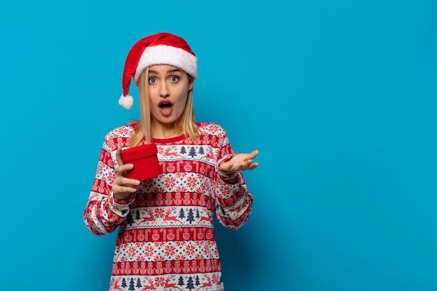 Blonde vrouw met kerstmuts voelt zich extreem geschokt en verrast, angstig en in paniek