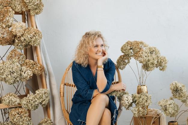 Blonde vrouw met krullend haar glimlacht en kijkt weg. om haar heen zijn ruimtes versierd met gedroogde hortensia's. concept van gelukkige mensen