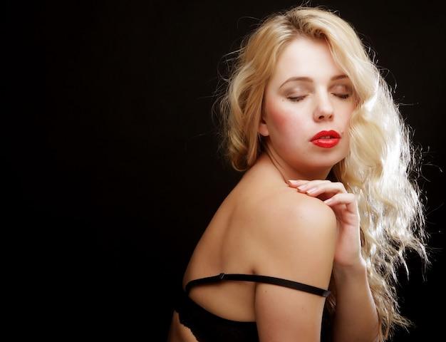 Blonde vrouw met krullend haar in zwarte lingerie