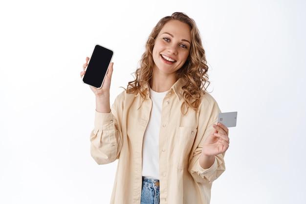 Blonde vrouw met krullend haar, laat een leeg smartphonescherm en creditcard zien, koopt internet, demonstreert een app, witte muur