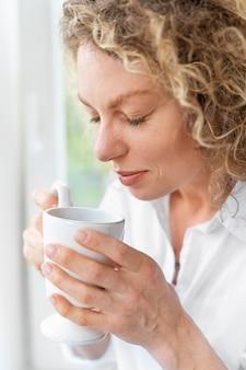 Blonde vrouw met krullend haar ontspannen thuis bij het raam
