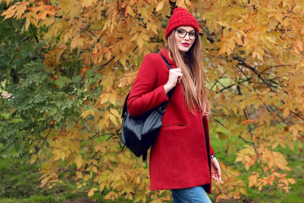 Blonde vrouw met lange haren wandelen in zonnige herfst park in trendy casual outfit.