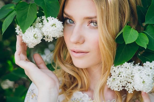 Blonde vrouw met lila bloemen in de lente