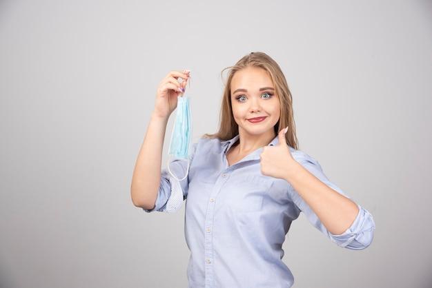 Blonde vrouw met medisch gezichtsmasker duim opdagen.