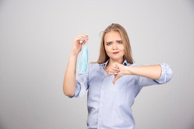 Blonde vrouw met medisch gezichtsmasker met duim naar beneden.