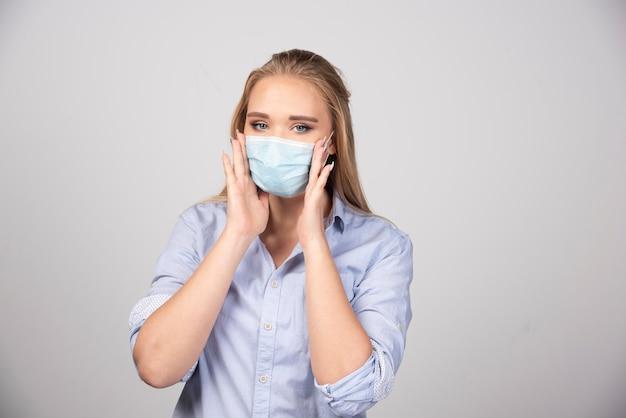 Blonde vrouw met medisch masker staat en kijkt.