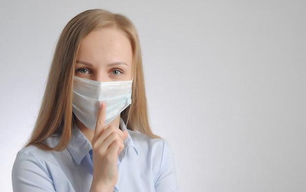 Blonde vrouw met medisch masker toont stilte en wees stil gebaar