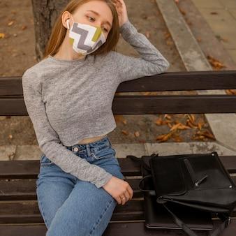 Blonde vrouw met medisch masker zittend op een bankje