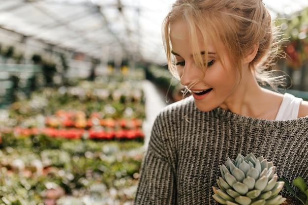 Blonde vrouw met mol boven haar lip houdt sappig. vrouw in grijze trui poseren in plantenwinkel.
