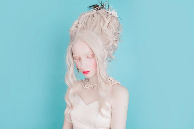 Blonde vrouw met mooie luxe rococo kapsel in witte jurk op een blauwe achtergrond