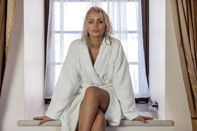 Blonde vrouw met nat haar in een badjas
