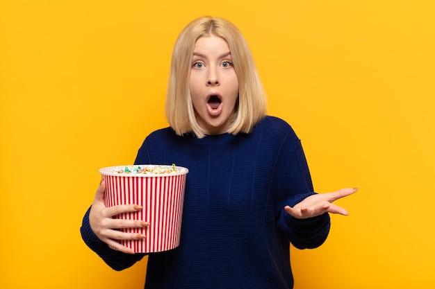 Blonde vrouw met open mond en verbaasd, geschokt en verbaasd over een ongelooflijke verrassing