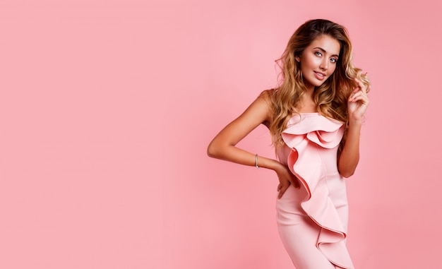 Blonde vrouw met perfect golvend kapsel in roze feestjurk poseren. hoge hakken.