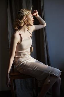 Blonde vrouw met sieraden oorbellen in haar oren zit bij het raam in de stralen van de avondzon. schoonheid gezicht mooi haar schone gladde huid, natuurlijke cosmetica en make-up, geen focus