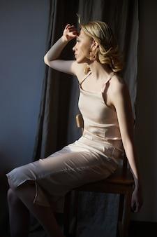 Blonde vrouw met sieraden oorbellen in haar oren zit bij het raam in de stralen van de avondzon.