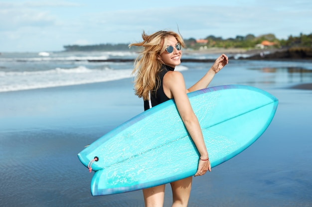 Blonde vrouw met surfplank op strand