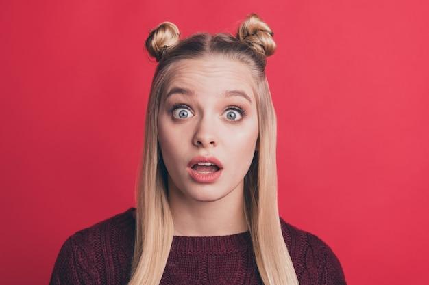 Blonde vrouw met top-knopen poseren tegen de rode muur