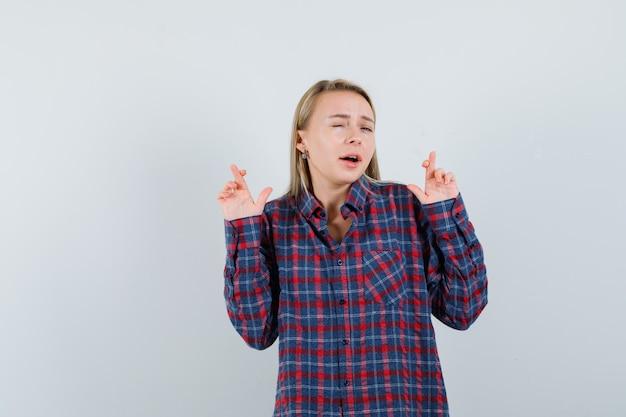 Blonde vrouw met vingers gekruist en knipogen in ingecheckte overhemd en op zoek naar optimistisch. vooraanzicht.