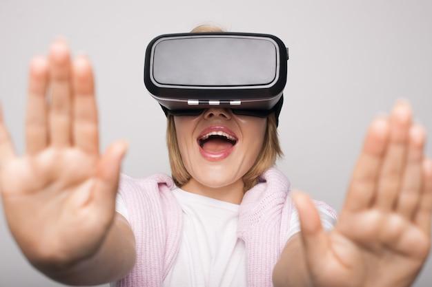 Blonde vrouw met virtual reality headset op hoofd is emotioneel op witte muur