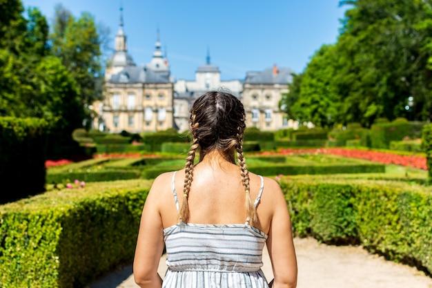 Blonde vrouw met vlechten op zoek naar het paleis van la granja de san idelfonso.
